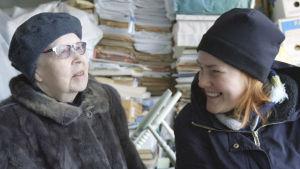 Sinikka och Vilja sitter och skrattar mellan tidningshögarna.