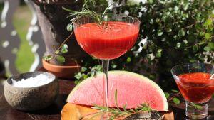 Röd drink i cocktailglas med rosmarinkvist, kumminfrön och melon i bakgrunden.