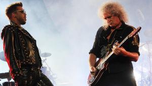 Adam Lambert ja Brian May (Queen) lavalla, Brian May soittaa kitaraa.