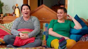 Sanna ja Pinja nauravat sohvalla.