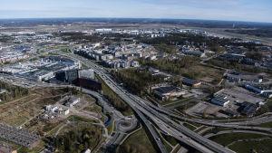 Flygbild över stadsdel med större moderna byggnader och en bred trafikled.