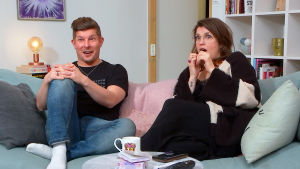 JarijaSanna istuvat sohvalla hämmentyneen näköisinä.