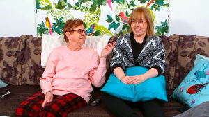 Marja ja Eija nauravat sohvalla.