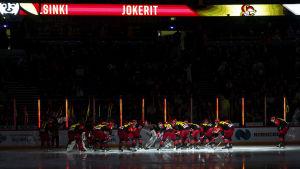 Jokeritspelarna samlade i en ring runt målet i ett mörkt Hartwall Arena.