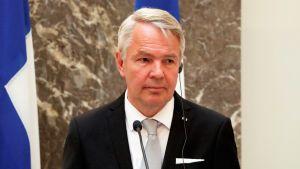 Pekka Haavisto med finska flaggor i bakgrunden.