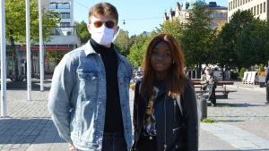 Ung man med munskydd bredvid mörkhyad ung kvinna.