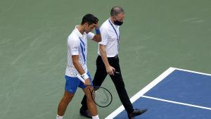 Novak Djokovic lämnar tennisplanen efter att han slagit till en boll som träffade och skadade en linjedomare.