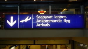 """En blå skylt med texten """"Ankommande flyg"""" på finska, svenska och engelska."""