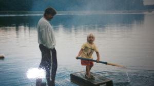 Krista Siegfrids som barn på en flotte med sin pappa.
