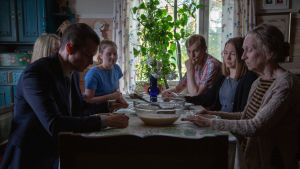 Johannes Holopaisen esittämä rikostutkija istuu ruokapöydässä lapsuudenkodissaan perheensä kanssa. Tunnelma näyttää kireältä.