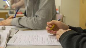 En elev skriver i sitt häfte i en skolklass.