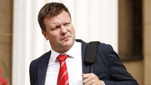 Minister Ville Skinnari med röd slips och mörkblå kavaj. Han håller i en  väskas rem med ena handen och tittar bort från kameran.