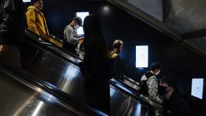 Personer i rulltrappan på en metrostation i Helsingfors centrum.