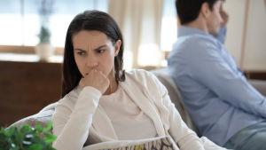 En kvinna sitter i en soffa och ser arg ut. I bakgrunden i anra ändan av soffan sitter en man med ansiktet bortvänt