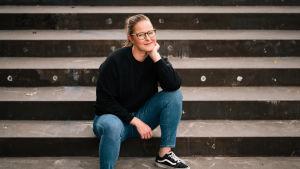 Ursula Herlin, Tilipäiväkirjat-sarjan päähenkilö istuu portailla ja katsoo kameraan.