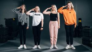 Neljä nuorta naista seisoo siviilivaatteissaan asennossa.