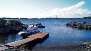 En båt som ligger förtöjd vid en brygga, men utsikt över Replotbron.