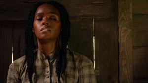 Huvudpersonen Eden trycker sig med skrämd blick mot väggen i sin barack.