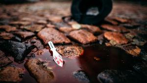 Mukulakiveyksellä pieni verilammikko, jossa on verinen veitsi. Taustala näkyy väärinpäin maassa oleva musta lierihattu.
