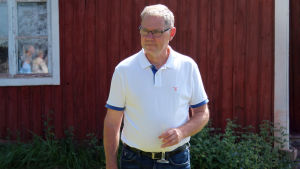 Stefan Friman står på gräsmattan utanför ett rödmålat hus en solig sommardag.