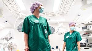 Två sjukskötare klädda i grönt och med munskydd arbetar i operationssal.