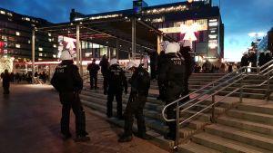 Poliser står och övervakar Nordiska motståndsrörelsen vid Narinkens torg i Helsingfors.