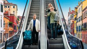 Kaksi eri suuntiin menevää liukuporrasta, keski-ikäinen mies tulee portaita alas kun samanikäinen nainen ja teinipoika menevät portailla ylös. Taustalla näkyy värikkäistä eurooppalaisia rakennuksia.