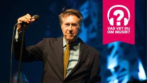 Bryan Ferry ler och håller högra handen på en mikrofon som är i en mikrofonställning.