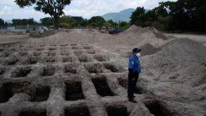 En polis i El Salvadors huvudstad San Salvador vid nygrävda gravar för pandemioffer. Bilden är tagen den 27 juli.
