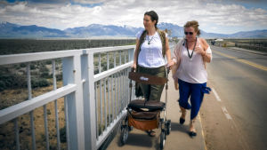 Två kvinnor promenerar på en vägbro. Den ena kvinnan går med rollator.