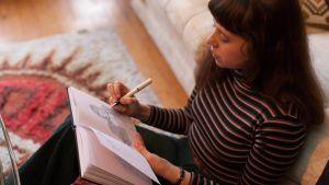 Nainen istuu sohvalla päiväkirjan kanssa kynä kädessään.