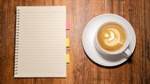 Pöydällä on muistivihko ja kupillinen kauniisti vaahdotettua kahvia.