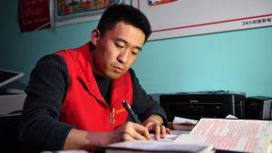 Mies kirjoittaa muistiinpanoja tai päiväkirjaa toimistopöydän ääressä.
