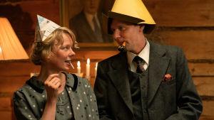 Tove (Alma Pöysti) och Atos Witanen (Shanti Roney) iklädda roliga hattar står och tittar på varandra.