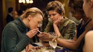 Tove (Alma Pöysti) får eld för sin cigarett medan Tuulikki Pietilä (Joanna Haartti) står bredvid och ser på.