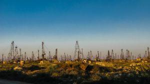 Tiotals oljeborrningstorn på ett oljefält utanför Azerbajdzjans huvudstad Baku.