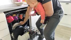 En pappa med sin baby i bärsele fyller diskmaskinen.