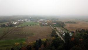 Flygfoto över åkrar och skog och en gård med ladugårdar och flera andra hus.