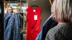 Lotta Palmgren tittar på sig själv i spegeln och håller upp ett klädplagg