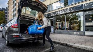 Minaa Seppälä plockar ut begagnade kläder ur bilen som hon ska sälja