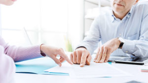 Två personer pekar på ett papper och samtalar.