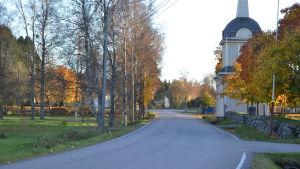 Väg som kurvar sig genom landskap i höstfärger, kyrkobyggnad till höger.