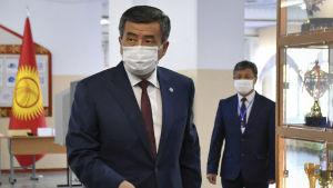 Sooronbai Jeenbekov pudottaa äänestyslipuketta vaaliuurnaan maski kasvoillaan