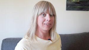 Kvinna sitter på soffa hemma hos sig i Jakobstad. Hon ser in i kameran.