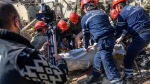 Räddningsarbetare tog hand om ett dödsoffer i rasmassorna i Ganja på söndag morgon.