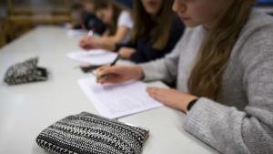 Elever sitter vid ett bord och gör uppgifter på papper.