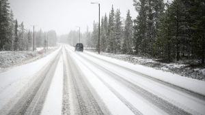 En bil kör på snöig väg i Kolari 17.10.2020 i samband med första snön.