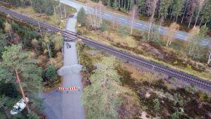 Plankorsningen i Skogby där det skedde en olycka i oktober 2017 mellan rälsbuss och militärfordon. Bilden visar platsen från luften med järnväg, grushögar och staket som stänger av korsningen.