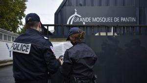 Bild på moské och två poliser som står utanför och läser en lapp med ryggarna mot kameran.