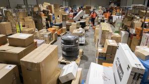 Paljon paketteja hallissa. Työntekijöitä lajittelemassa.